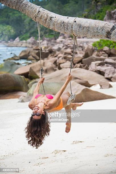 Young beautiful woman in a bikini swinging at a palmtree at white sandy Banana Beach on September 27 2015 in La Passe La Digue Seychelles
