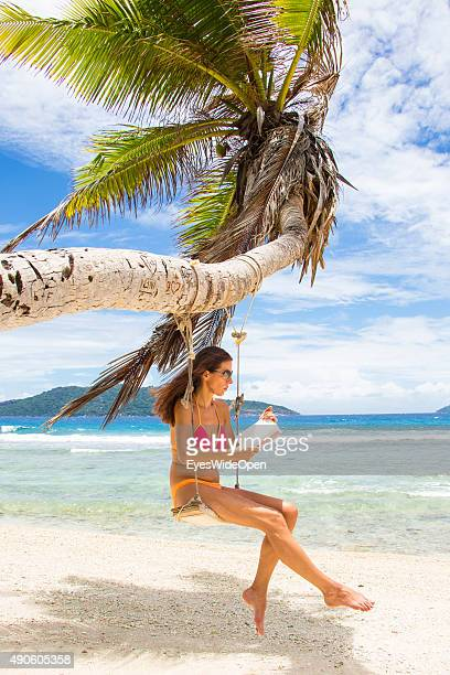 Young beautiful woman in a bikini swinging reading a book at a palmtree at white sandy Banana Beach on September 27 2015 in La Passe La Digue...