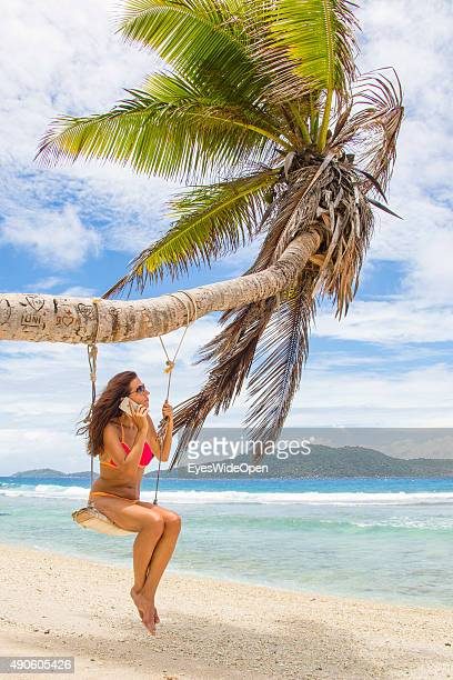 Young beautiful woman in a bikini swinging working making a telephone call with an apple iphone handy at a palmtree at white sandy Banana Beach on...