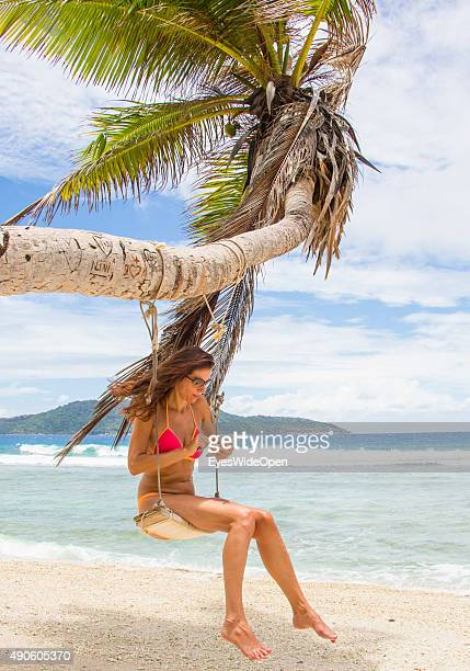 Young beautiful woman in a bikini swinging working sending a sms message with an apple iphone handy at a palmtree at white sandy Banana Beach on...