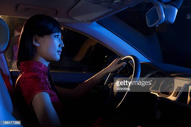 Young beautiful woman in a traditional Chinese dress driving at night