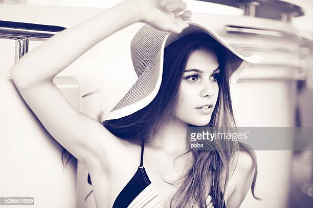 Young beautiful woman in swimsuit posing on yacht