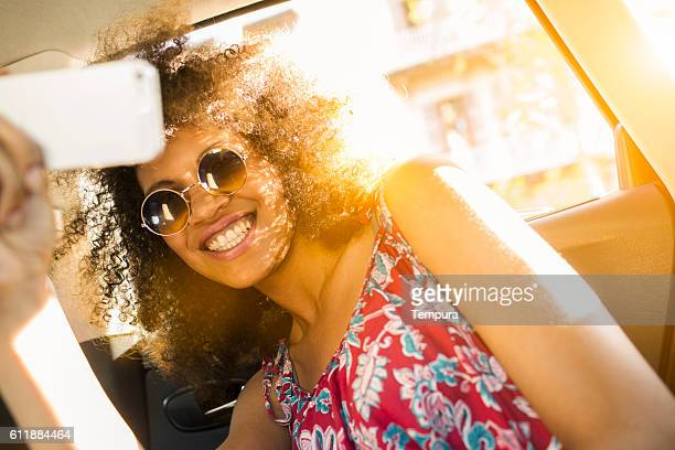 Young beautiful woman in taxi and using a phone