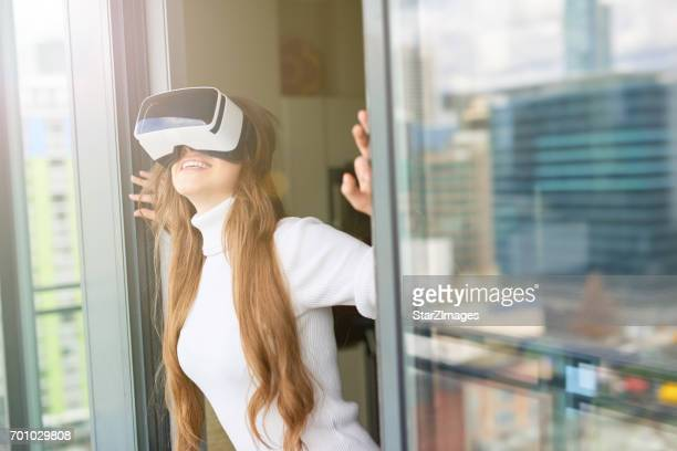 Young beautiful woman in virtual reality glasses on balcony