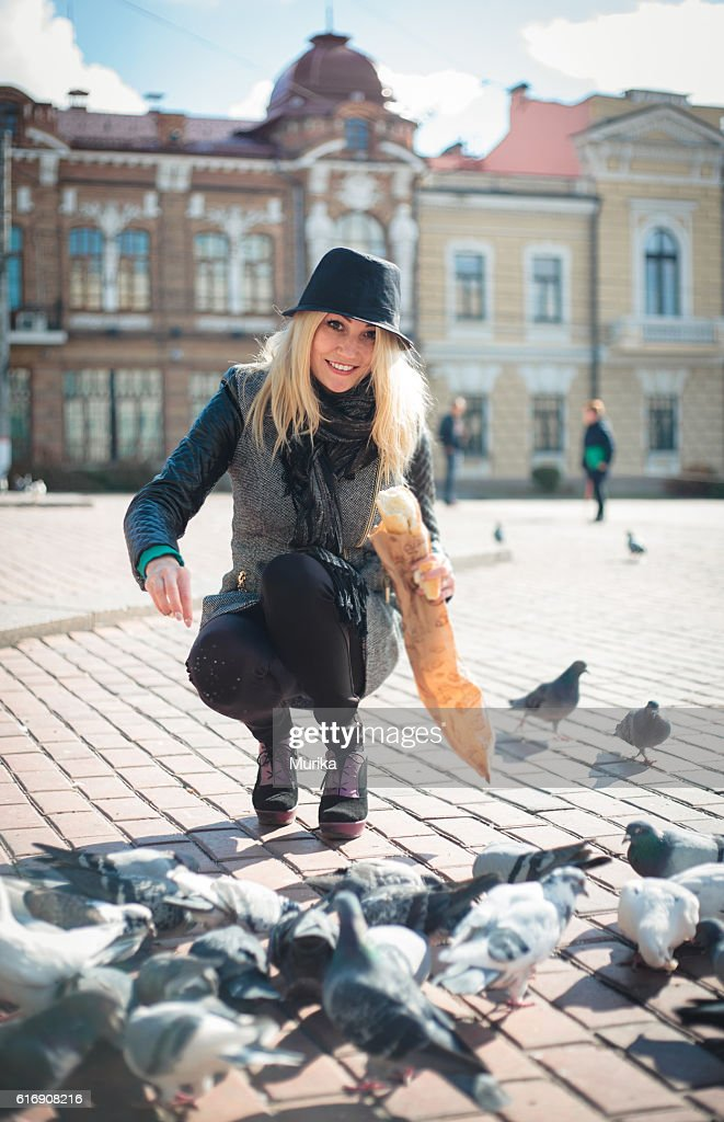 Young beautiful woman is feeding pigeons with bread crumbs in : Stock Photo