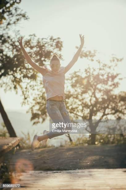 Young beautiful woman jumping for joy