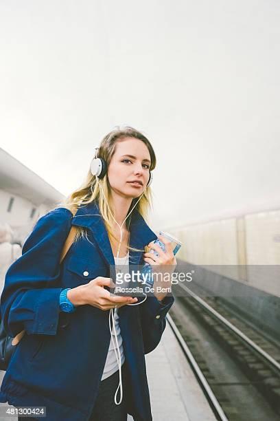 Junge schöne Frau hören Musik und warten auf U-Bahn