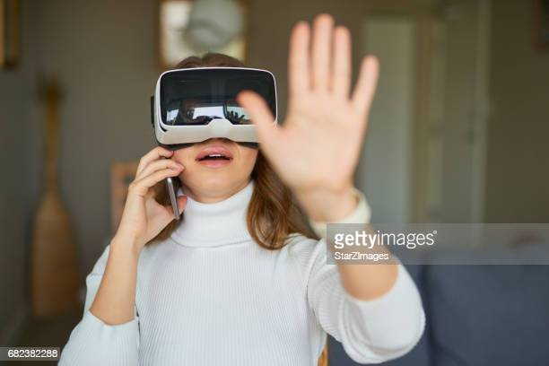 Young beautiful woman making a call while wearing virtual reality headset