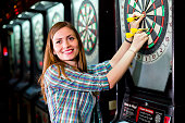Young beautiful woman playing darts in a club and smiling