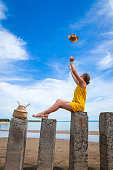 Young beautiful woman in a light casual dress resting,throws a straw hat into the sky  and posing on rocks on a sandy beach near a blue sky on a summer day, beautiful sea against a blue sky