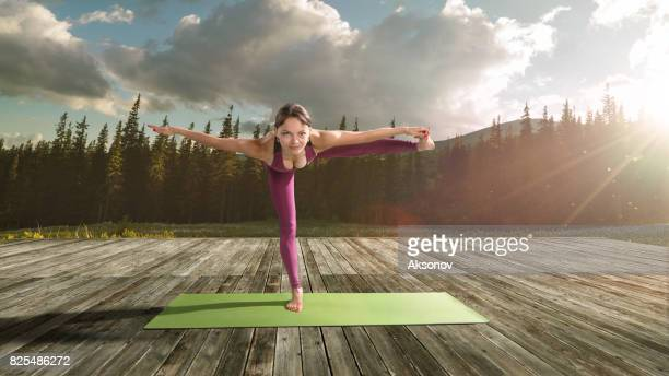 Young beautiful woman practicing outdoors yoga. Balancing stick