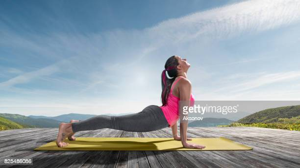 Young beautiful woman practicing outdoors yoga. Cobra