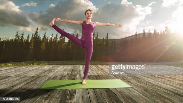 Young beautiful woman practicing outdoors yoga. Extended Hand-To-Big-Toe Pose