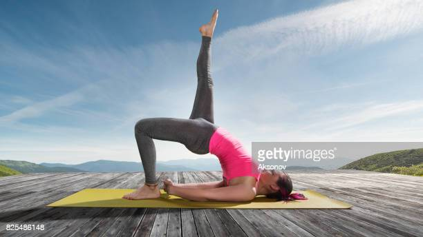 Young beautiful woman practicing outdoors yoga