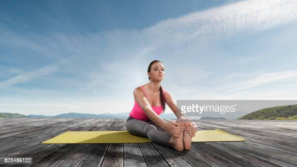 Young beautiful woman practicing outdoors yoga. Seated forward fold