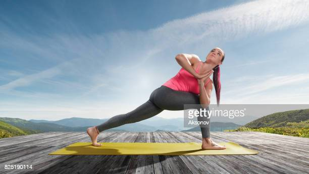 Young beautiful woman practicing outdoors yoga. Triangle