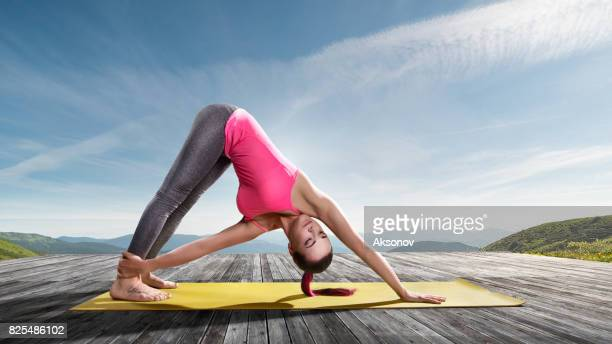 Young beautiful woman practicing outdoors yoga. Twisting triangle