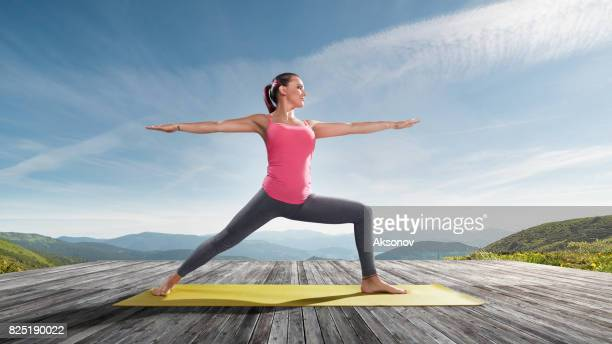 Young beautiful woman practicing outdoors yoga. Warrior