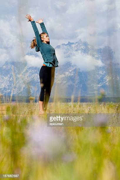 Young beautiful woman practicing yoga in a green field