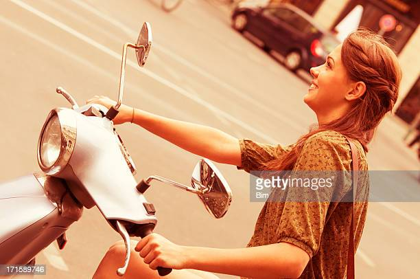 Young Beautiful Woman Riding Scooter on City Street