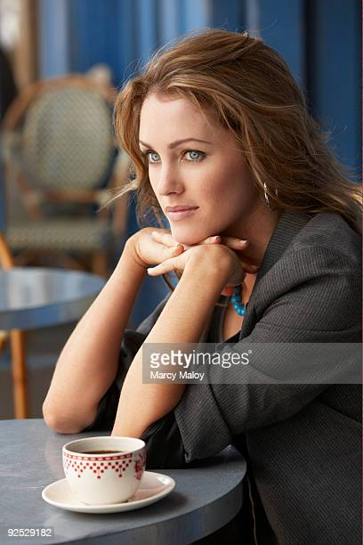Young beautiful woman sitting at cafe with coffee.