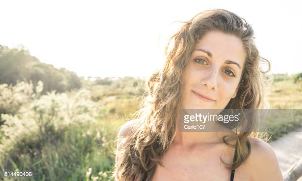 Young beautiful woman smiling at the sunset in the Tuscan countryside