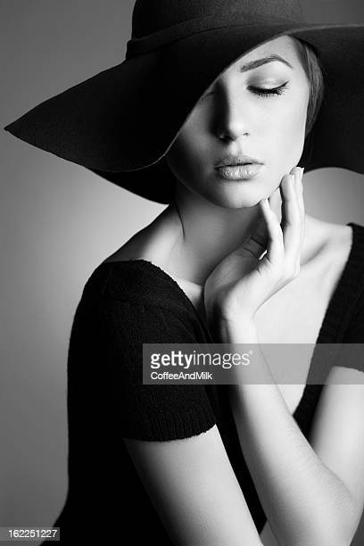 Young beautiful woman wearing hat on dark background