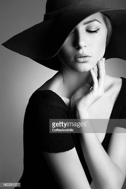 Jeune Belle femme portant un chapeau sur fond sombre