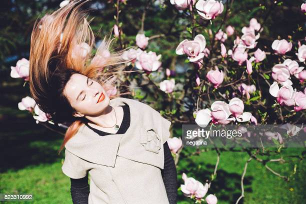 young beautiful woman winnows her colored hair in front of blossoming magnolia tree