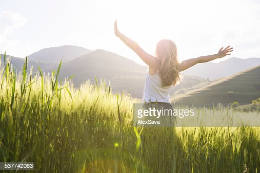 young beautiful woman with hands raised in the wheat field