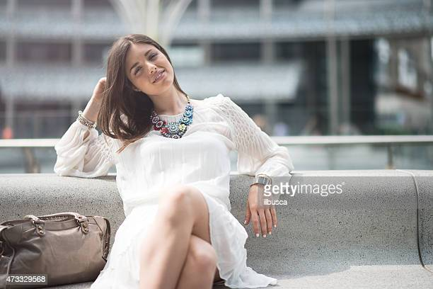Young beautiful woman with white dress relaxing on bench