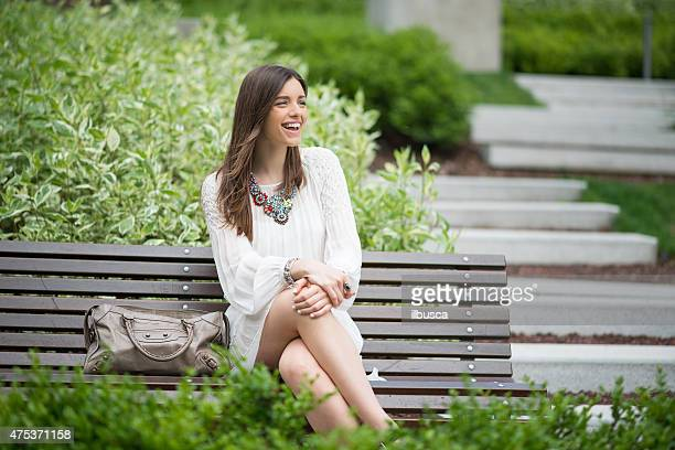 Young beautiful woman with white dress sit on bench