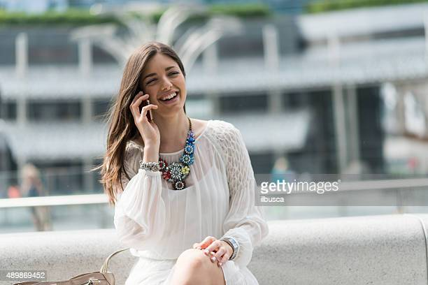 Young beautiful woman with white dress using mobile smartphone
