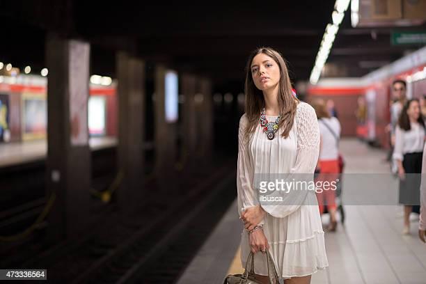 Jeune Belle femme avec robe blanche attente pour le métro