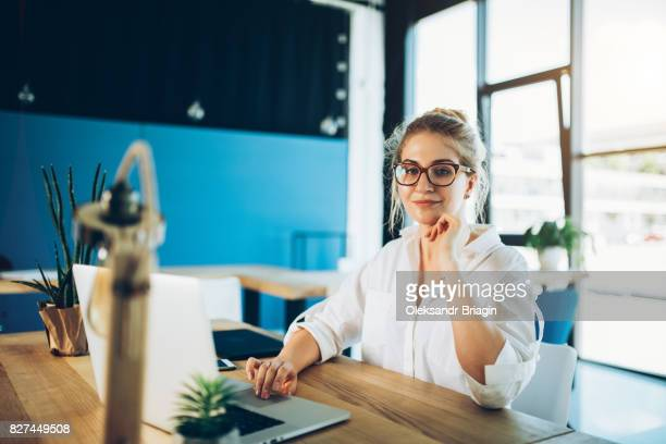 Young beautiful woman working at the office with laptop