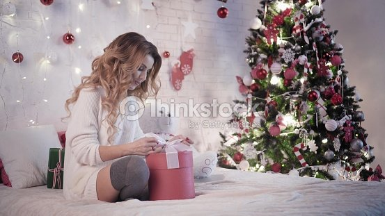 Young Beautiful Woman Wraps Christmas Gifts Sitting On The Bed Near ...