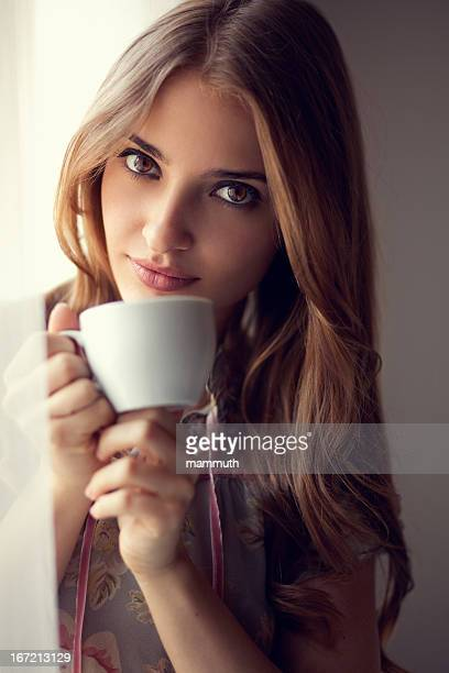 Jovem Beleza beber café pela janela