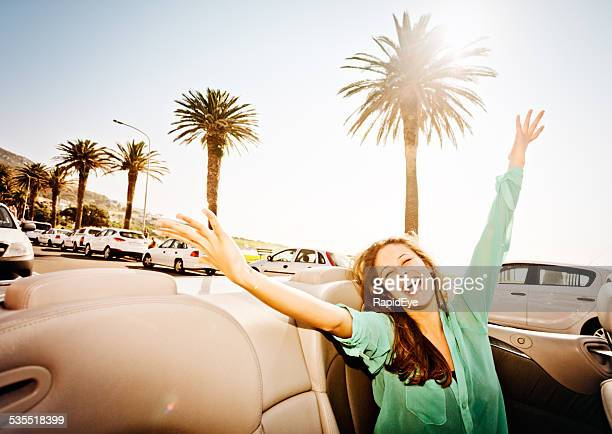 Young beauty in convertible driving on seaside promenade waves delightedly