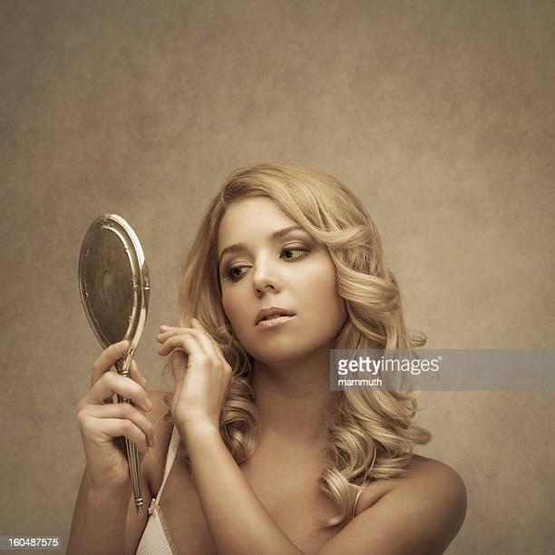 Junge Schönheit lookin an sich in einem silbernen hand mirror