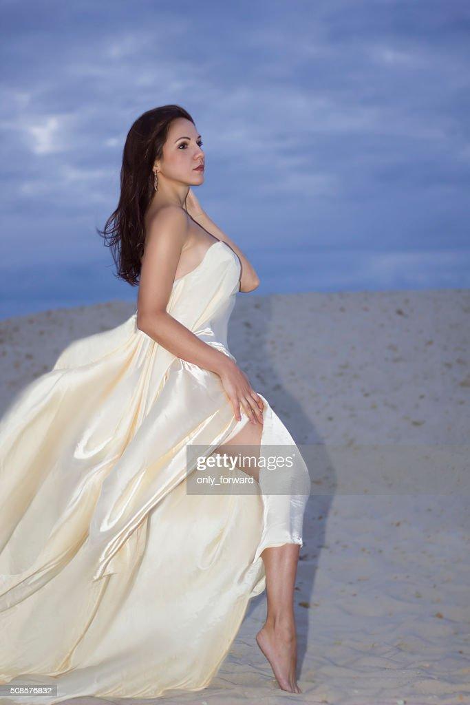Young beauty woman in fluttering beige dress : Stock Photo