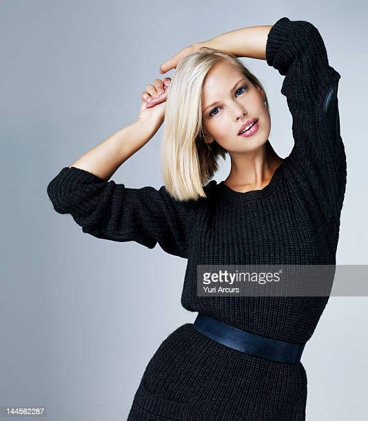 Young beauty woman posing with hands above head, studio shot