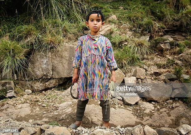 A young Berber girl holds her syth and a clump of grass in the village of Ikkiss on July 29 2007 near Imlil Morocco Young girls such as this are put...