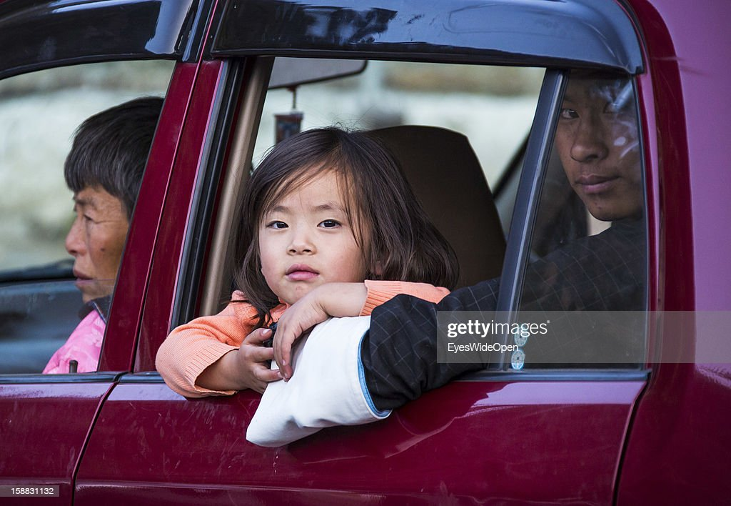 Young bhutanese girl with her family in a car, visit a marketplace on November 18, 2012 in Thimphu, Bhutan.