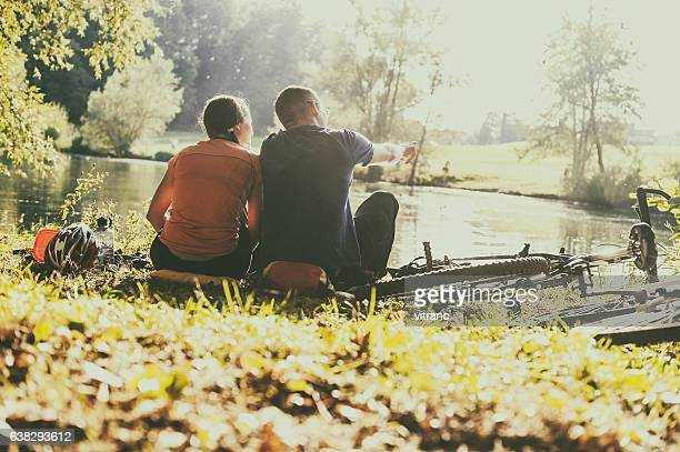 Young bikers couple sitting on the grass