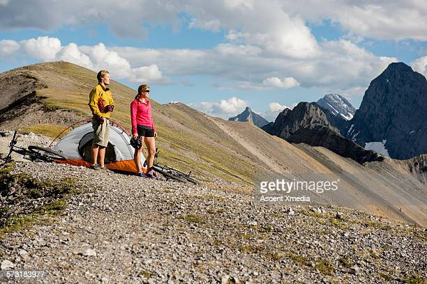 Young biking couple look off from ridge campsite