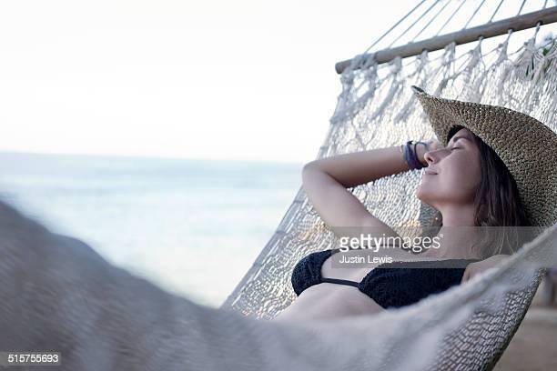 Young Bikini Clad Woman Naps in Beach Hammock