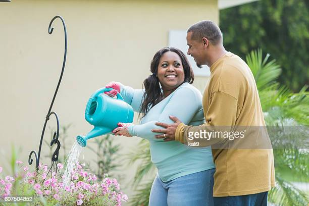 Young black couple gardening, watering flowers