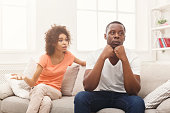 Young african-american couple quarreling at home, man offended. Family relationship difficulties concept, copy space