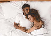 Lovely black couple lying in white bed, sleeping together, top view