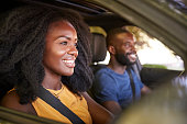 Young black couple smiling in a car during a road trip